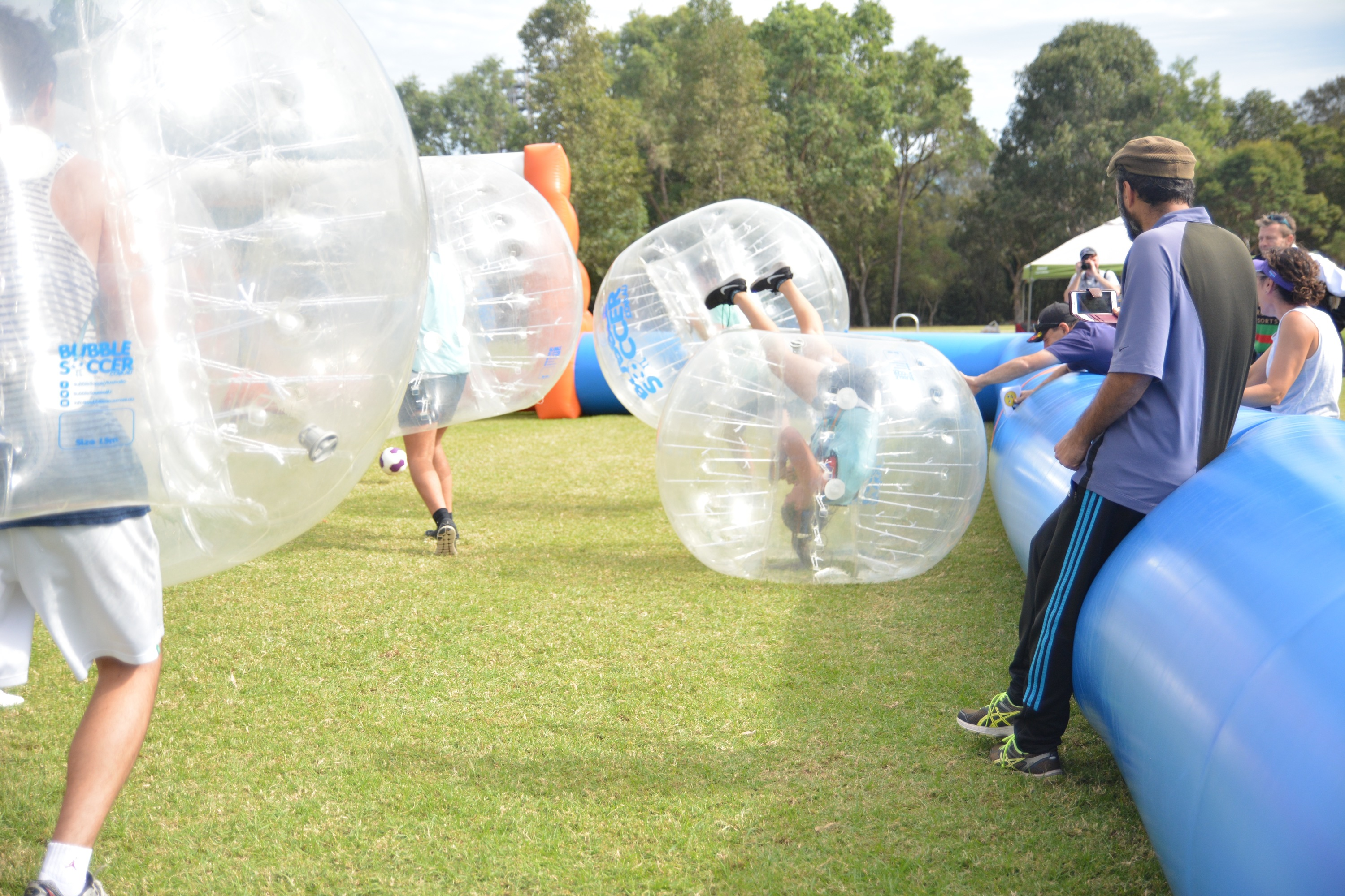 People rolling around playing bubble soccer.