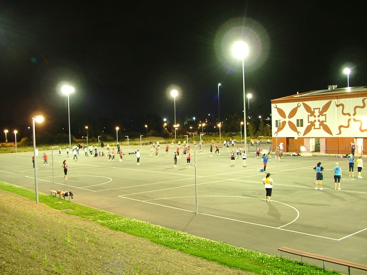 People playing on a netball court.