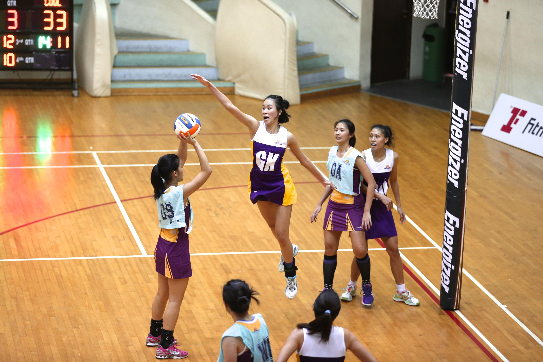 Woman playing netball, defending.