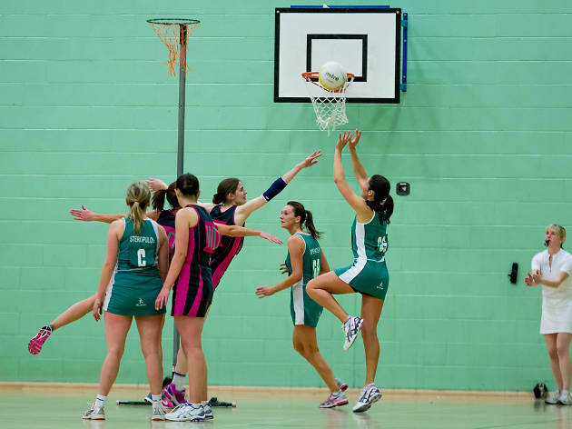 Woman shooting in a game of netball.