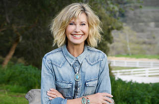 Olivia Newton-John with rocks double denim standing in front of greenery.