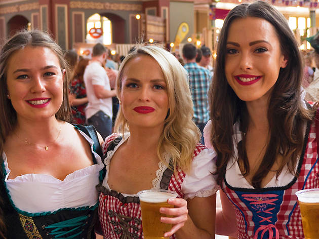 Three women in German costumes with beer