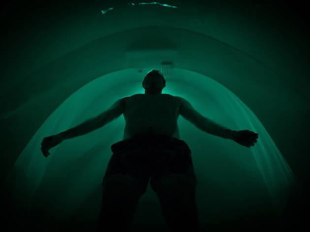 Man floats inside dark pod.