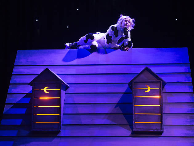 A person in a cat costume sits on a barnyard roof.