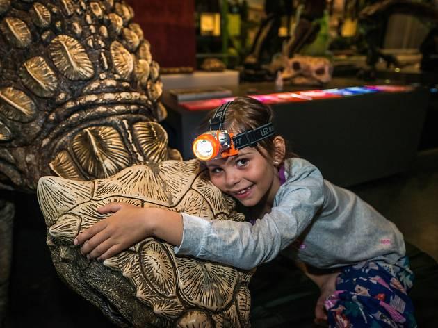 Kid hugs model dinosaur.