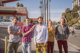 band standing in front of a motel on a sunny street