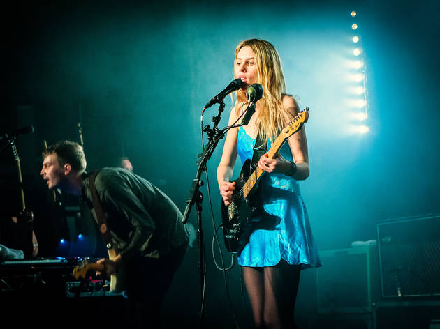 Wolf Alice on stage playing the guitar