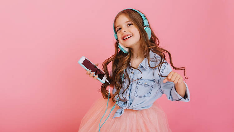 Little girl with long hair holding onto an iPhone with green headphones dancing while wearing a pink tutu and denim shirt while standing in front of a pink wall