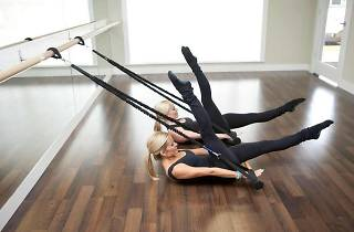 Three women doing barre exercises in a studio