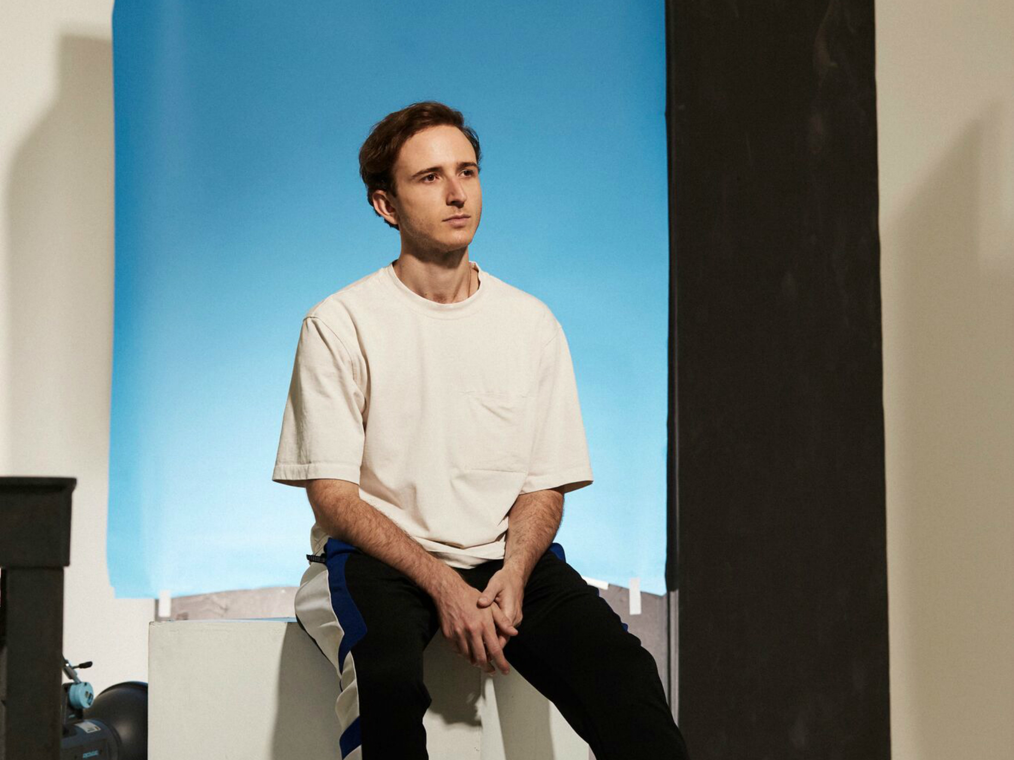 Press release photo of RL Grime sitting on plinth in front of blue background