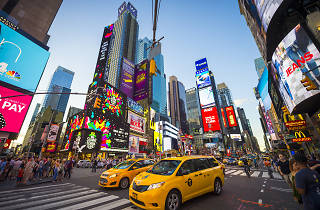 Times Square in NYC with brightly colored billboards and yellow cabs on the street and blue skies