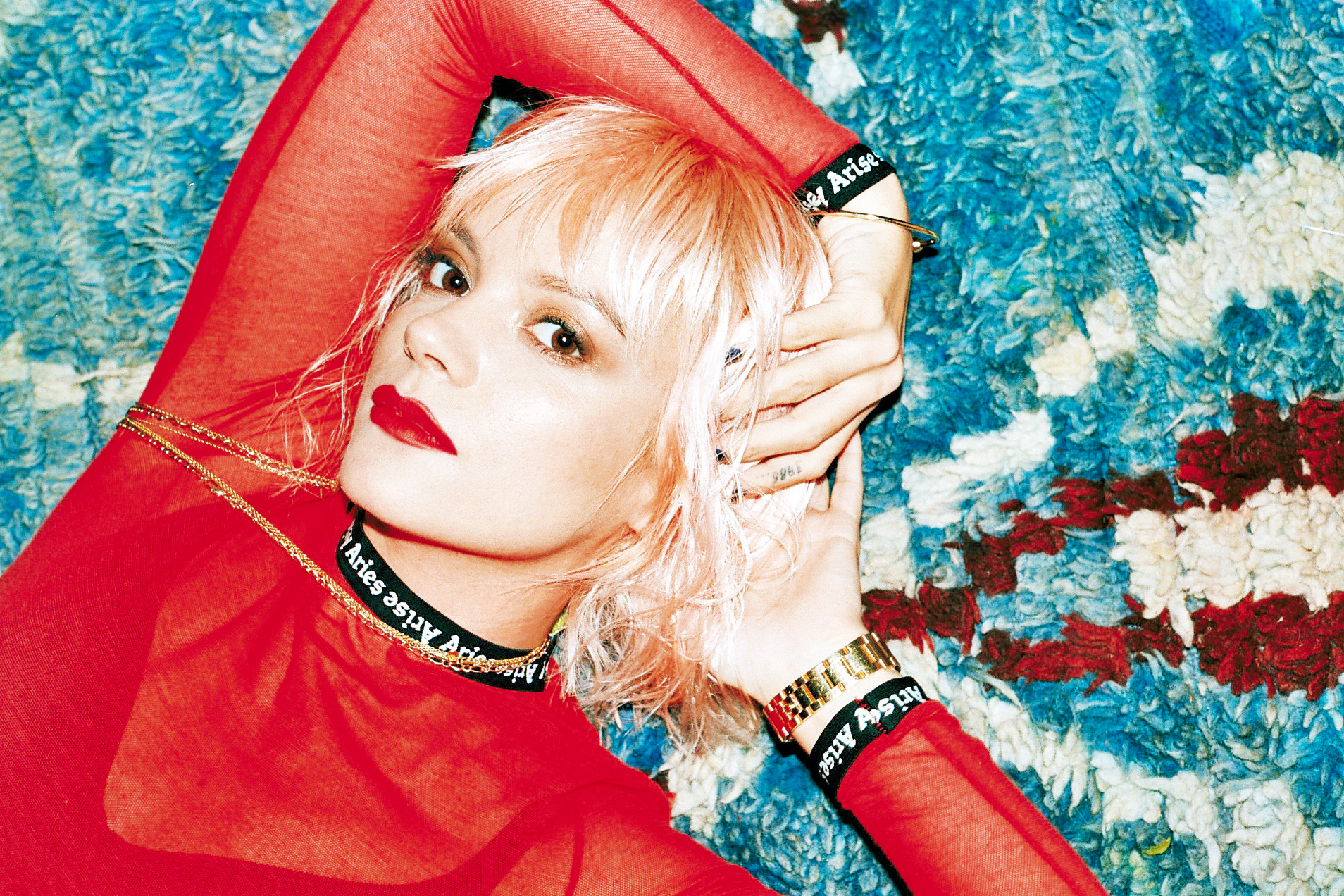 Lily Allen wearing a red top in press shot