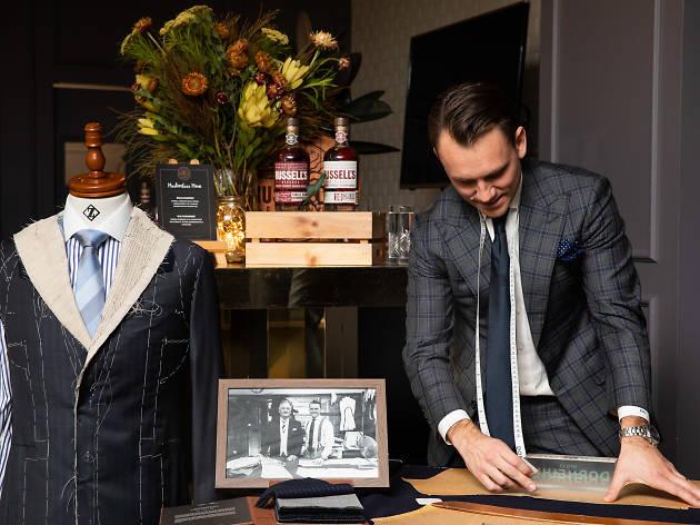 A tailor measures a suit.
