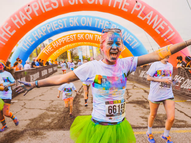 People cross the finish line, running through colour.
