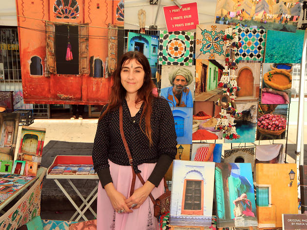 Woman stands in front of a colourful market stall.