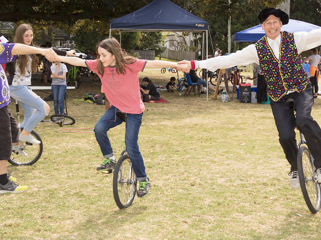 People ride on unicycles at a fair.