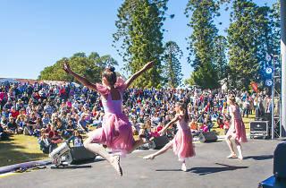 Children perform ballet for an outdoor crowd.