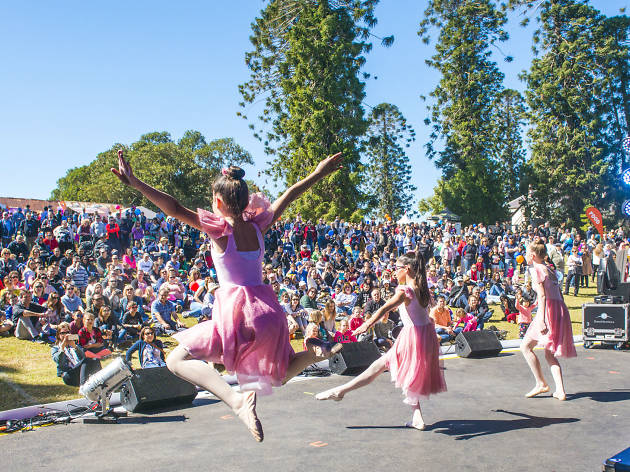 Children perform ballet for an outdoor crowd.