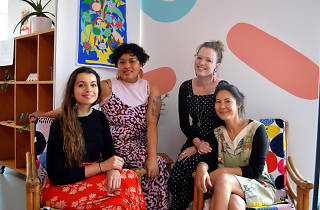 Ladies sit in a colourful room.