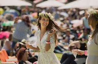 Woman walks through a crowd with a glass of bubbles.