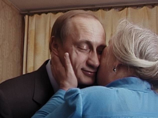 Russian president Vladimir Putin is kissed on the cheek by an elderly woman.
