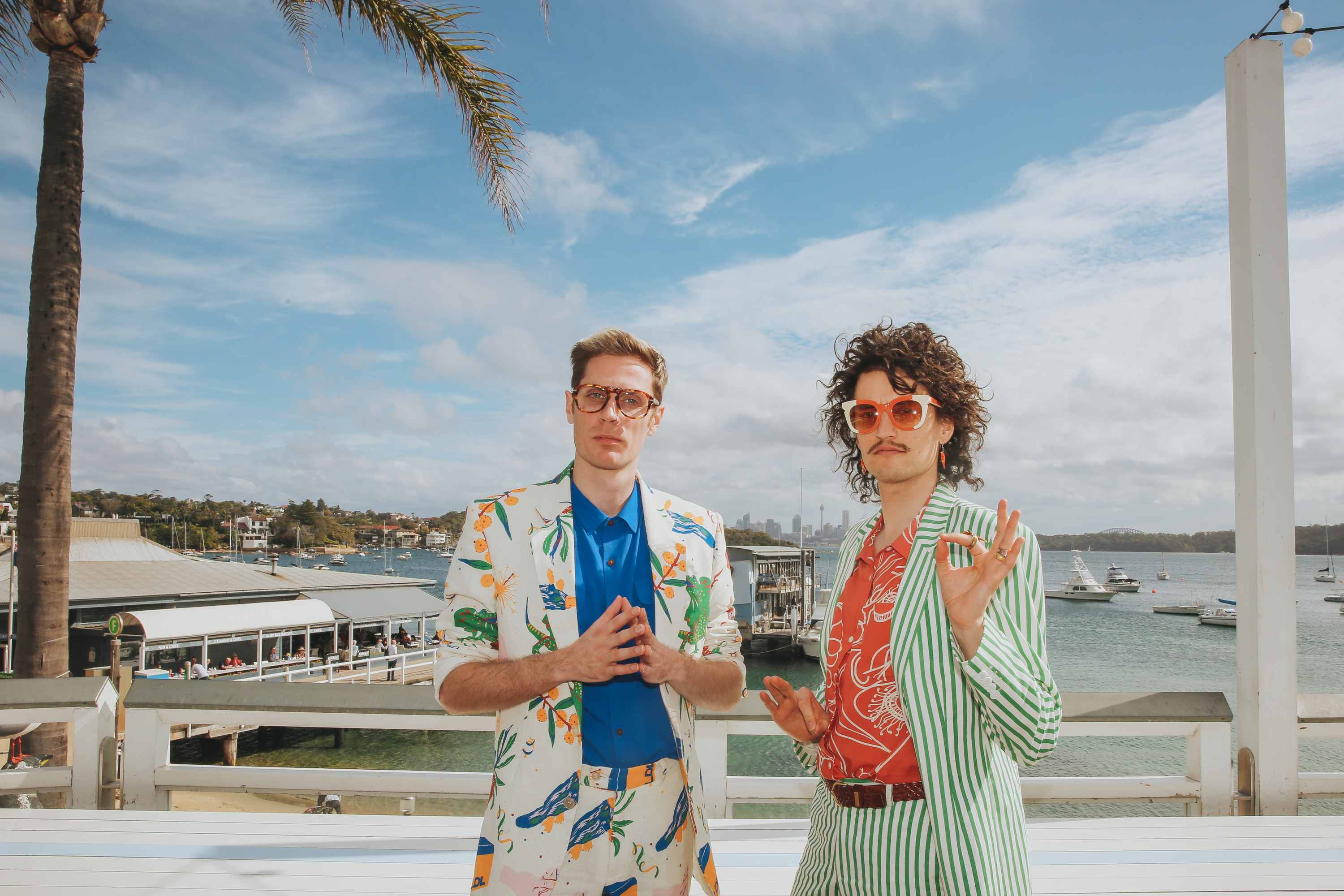 The band members stand on a deck in front of the beach.