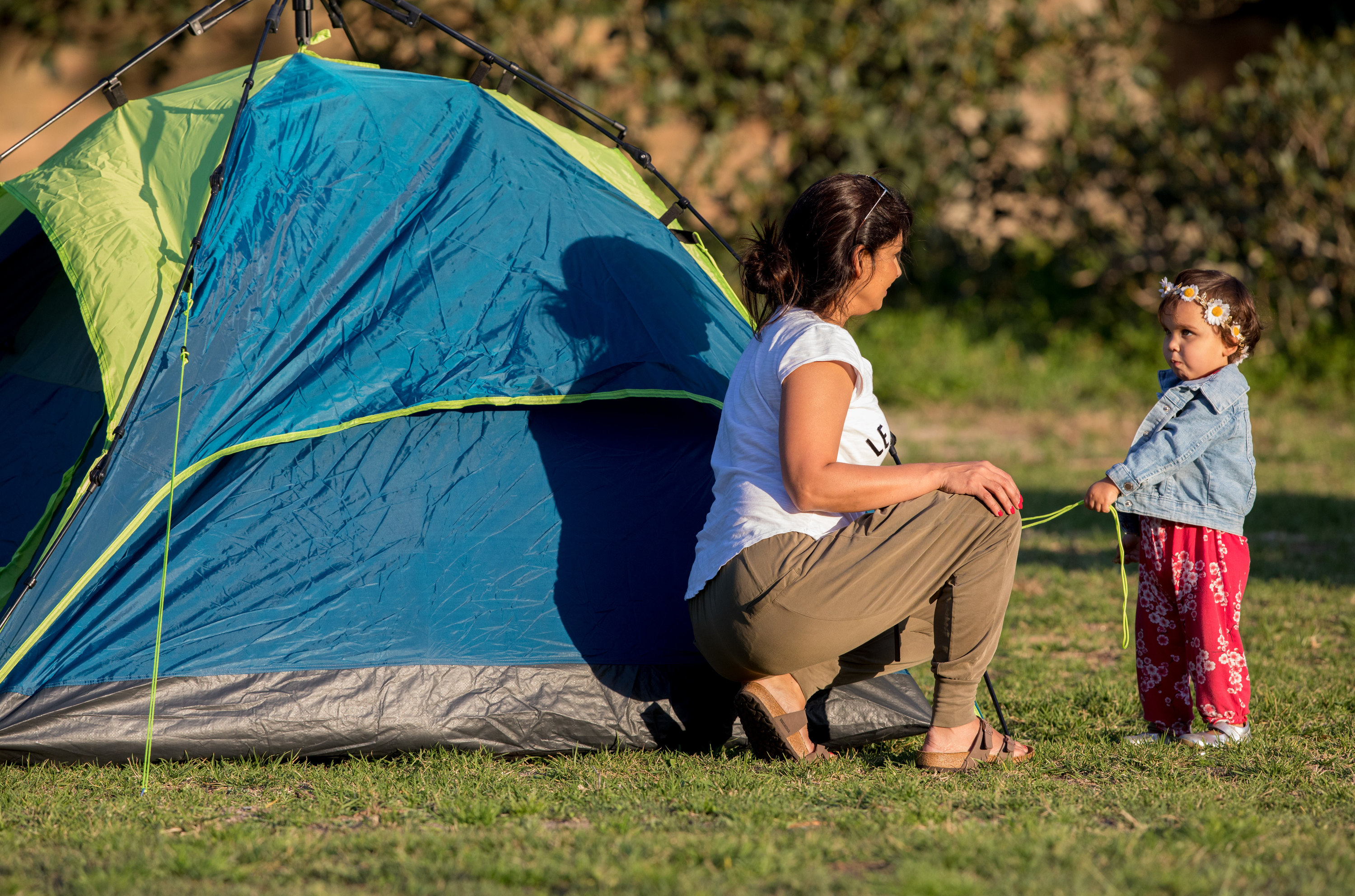 A woman and child sit by a tent.