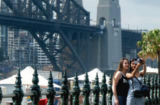 Tourist taking photos in front of the Sydney Harbour Bridge