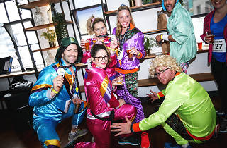 People dressed in colourful exercise costumes in a bar.