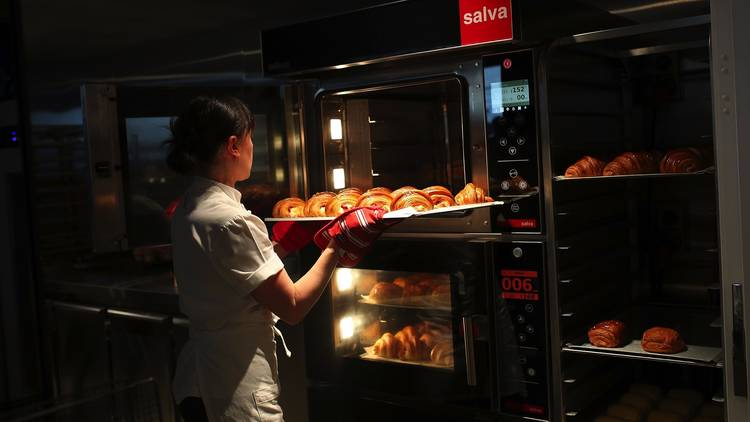 Putting croissants in oven at Lune Collins Street
