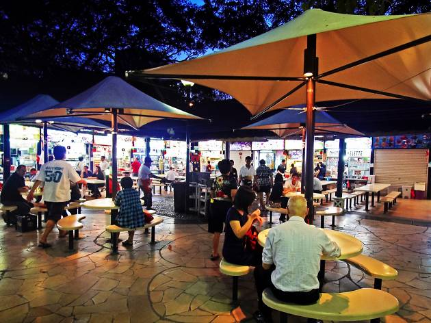 Night shot of people dining under the canopies with stalls in the background