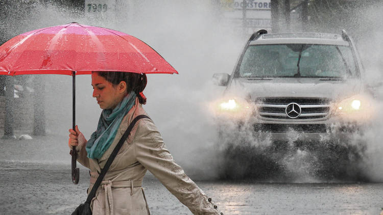 Person being splashed by car in the rain