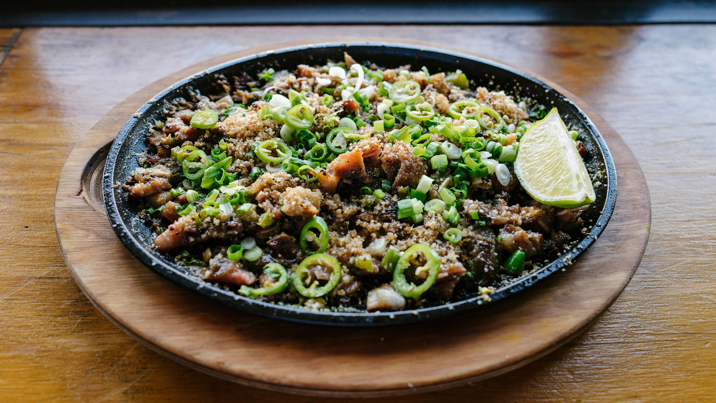 <p>Sizzling pork sisig with sweetbreads and calamansi</p>