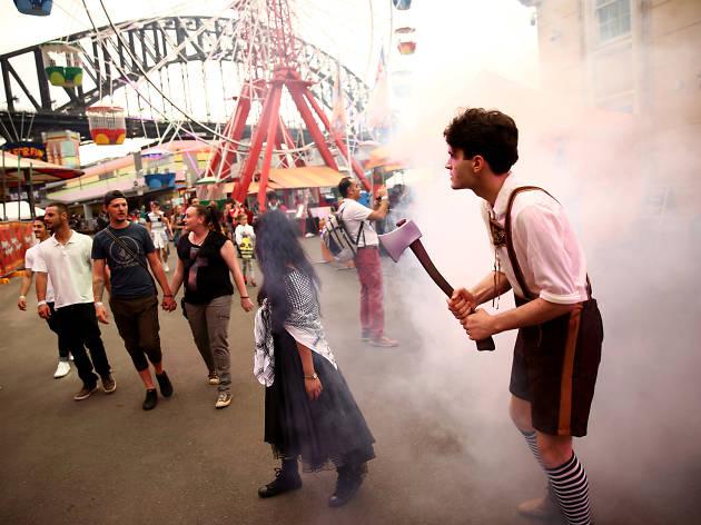 People walk through Luna Park at Halloween.