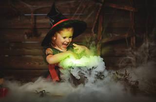 Child plays with fake cauldron.