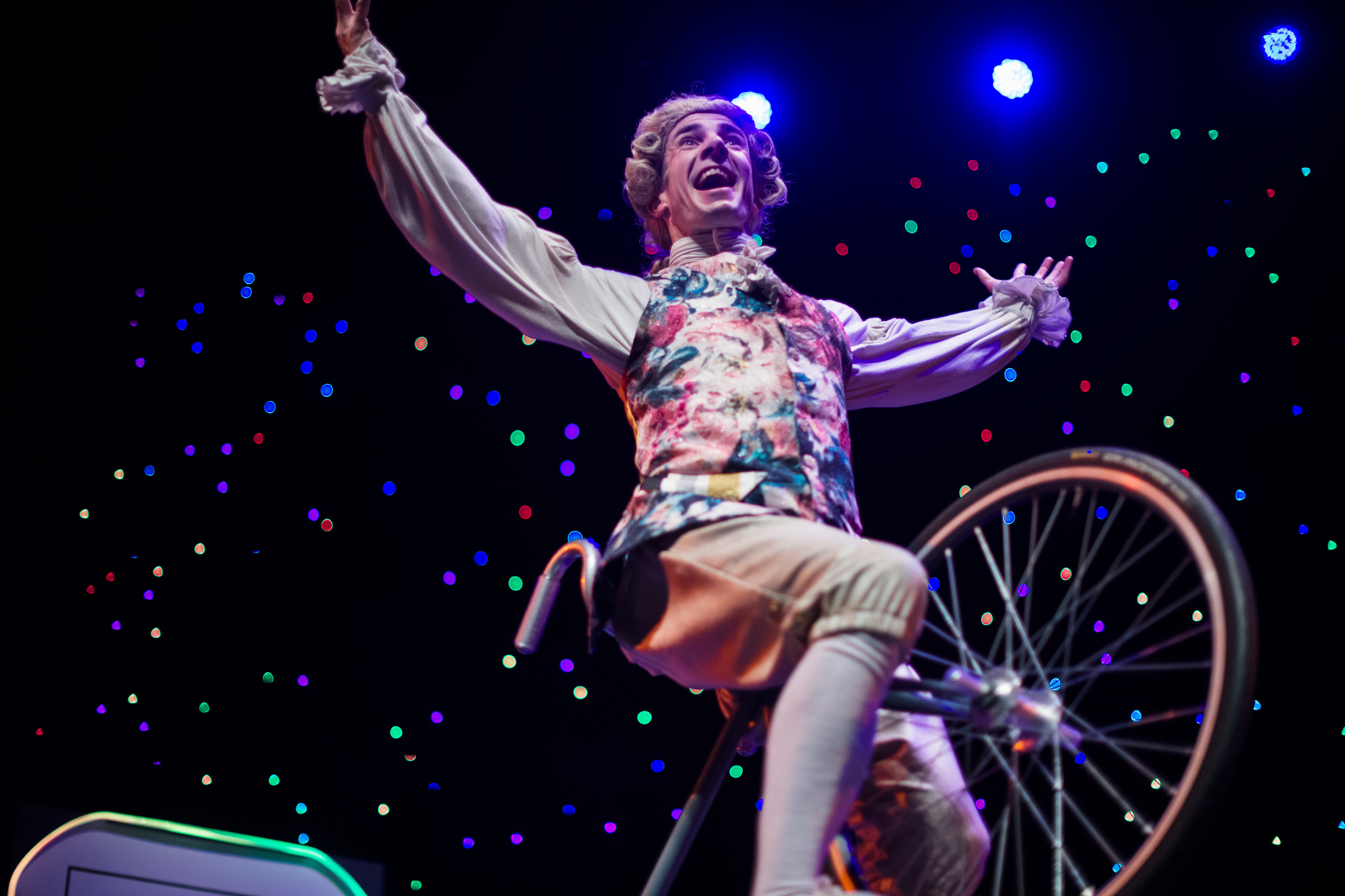 Man rides a unicycle dressed as Mozart.