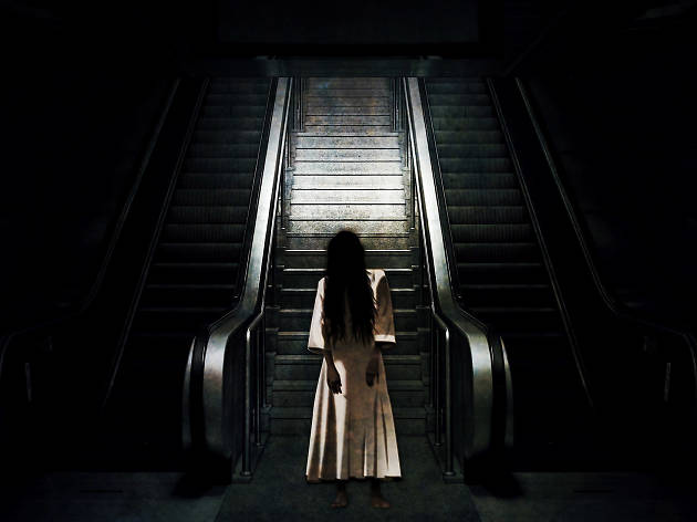 Creepy woman stands in front of escalator.