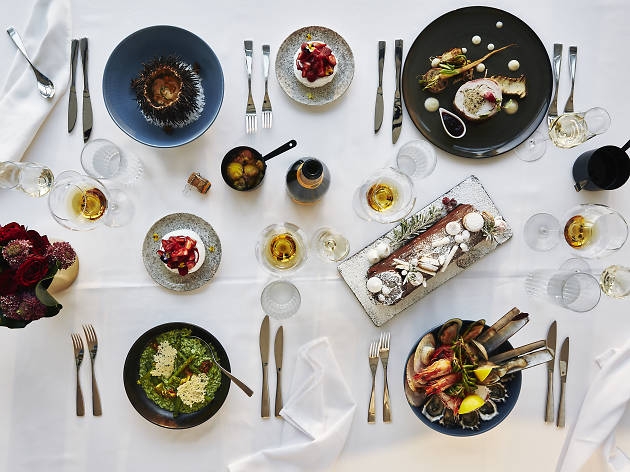 A table laid with lots of food and wine