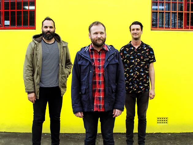 Band members stand in front of a yellow wall.