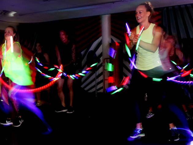 People dancing with glow sticks in the dark