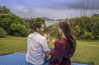 Man and woman drink Champagne overlooking the city skyline.