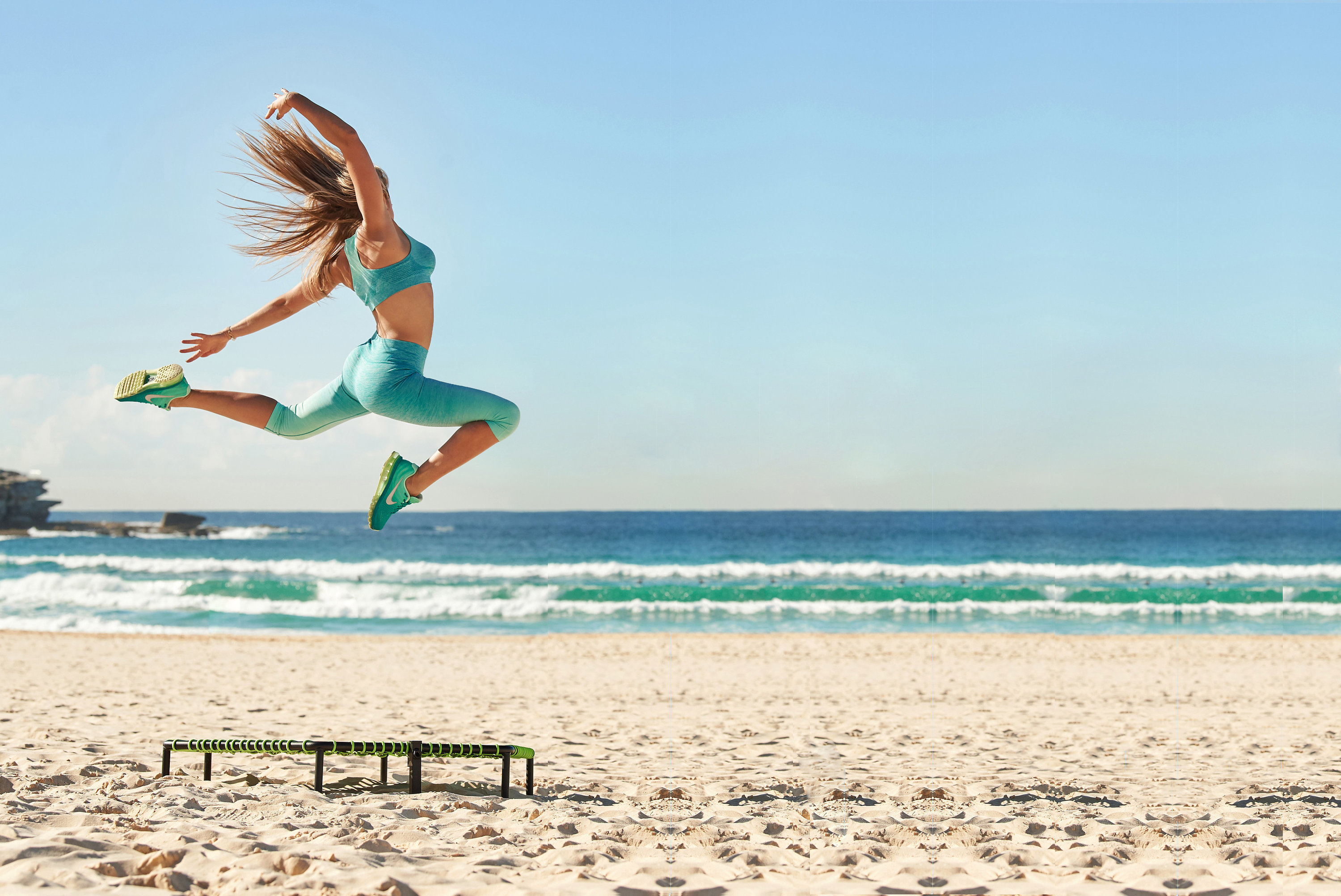 Woman jumping on trampoline on the beach.