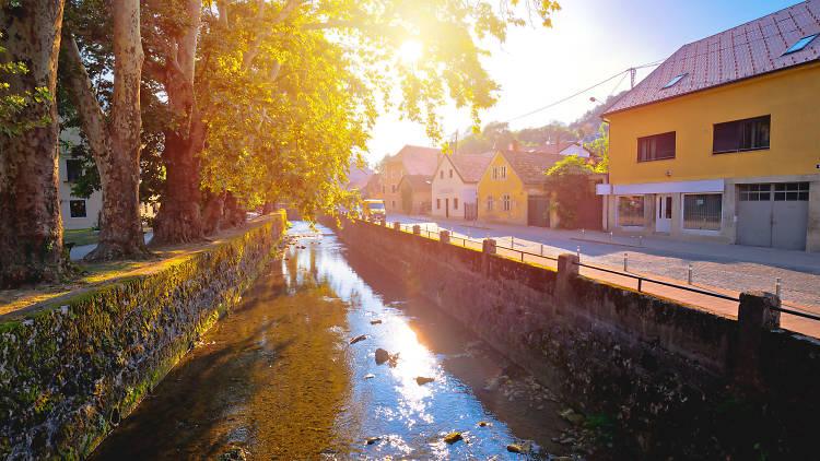 Town of Samobor river and park sun haze view