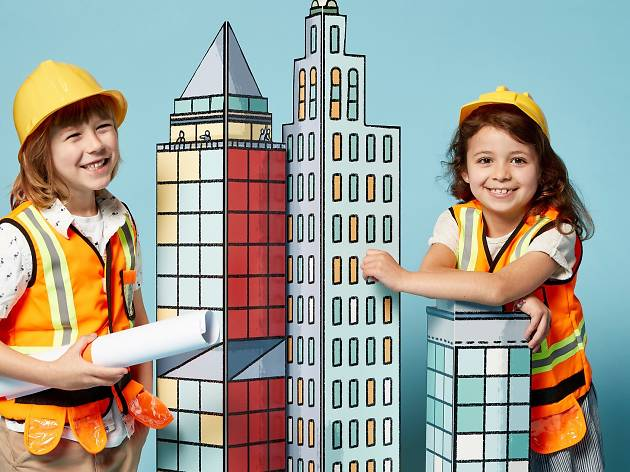 Kids play with building cut-outs.