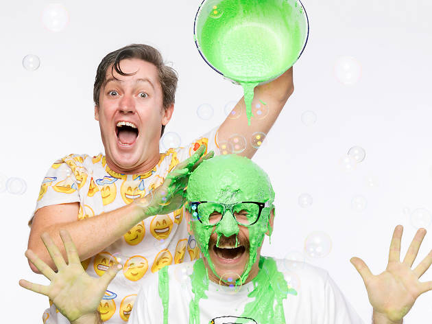 One man pours green slime on another.