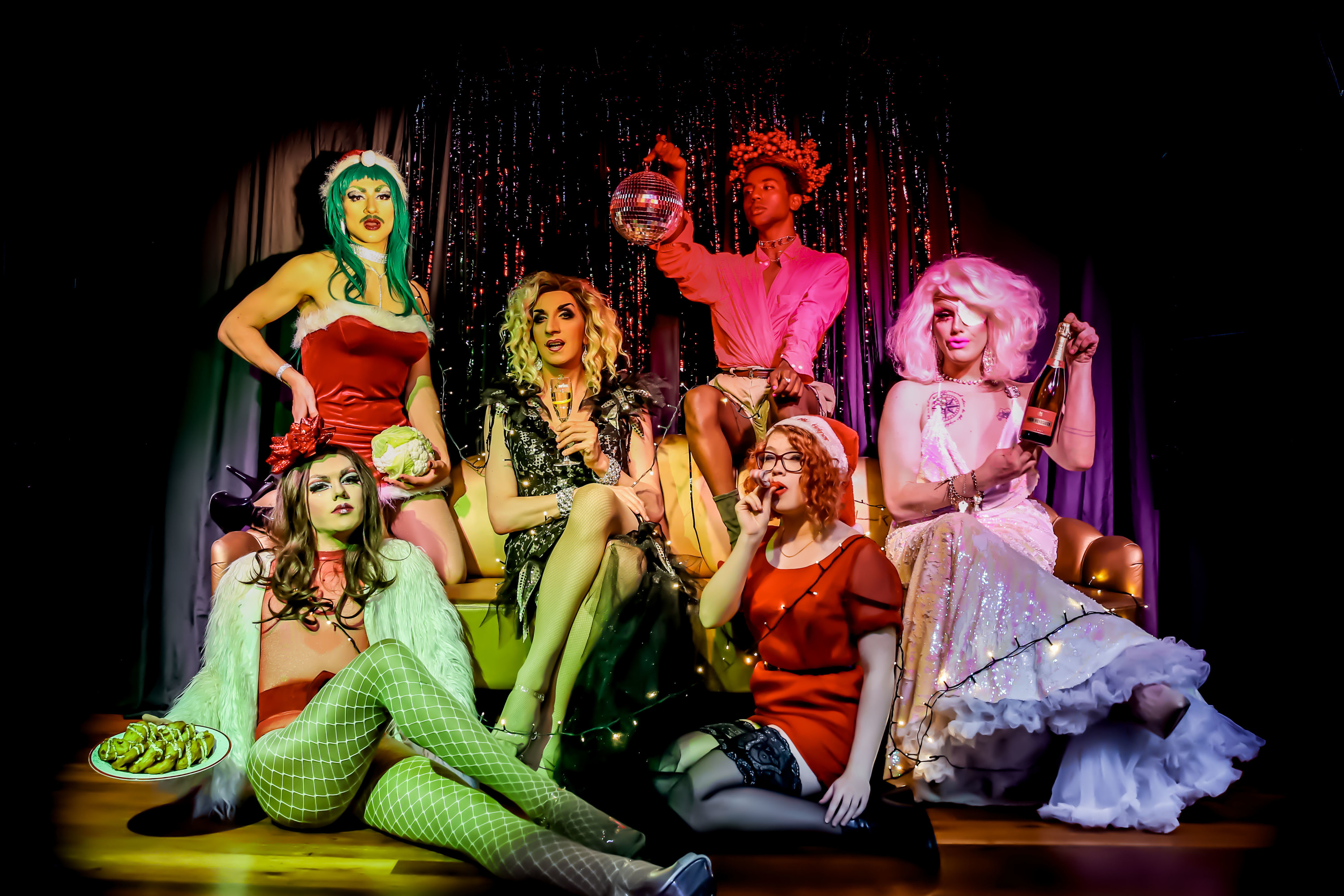 Drag queens pose in Christmas outfits.