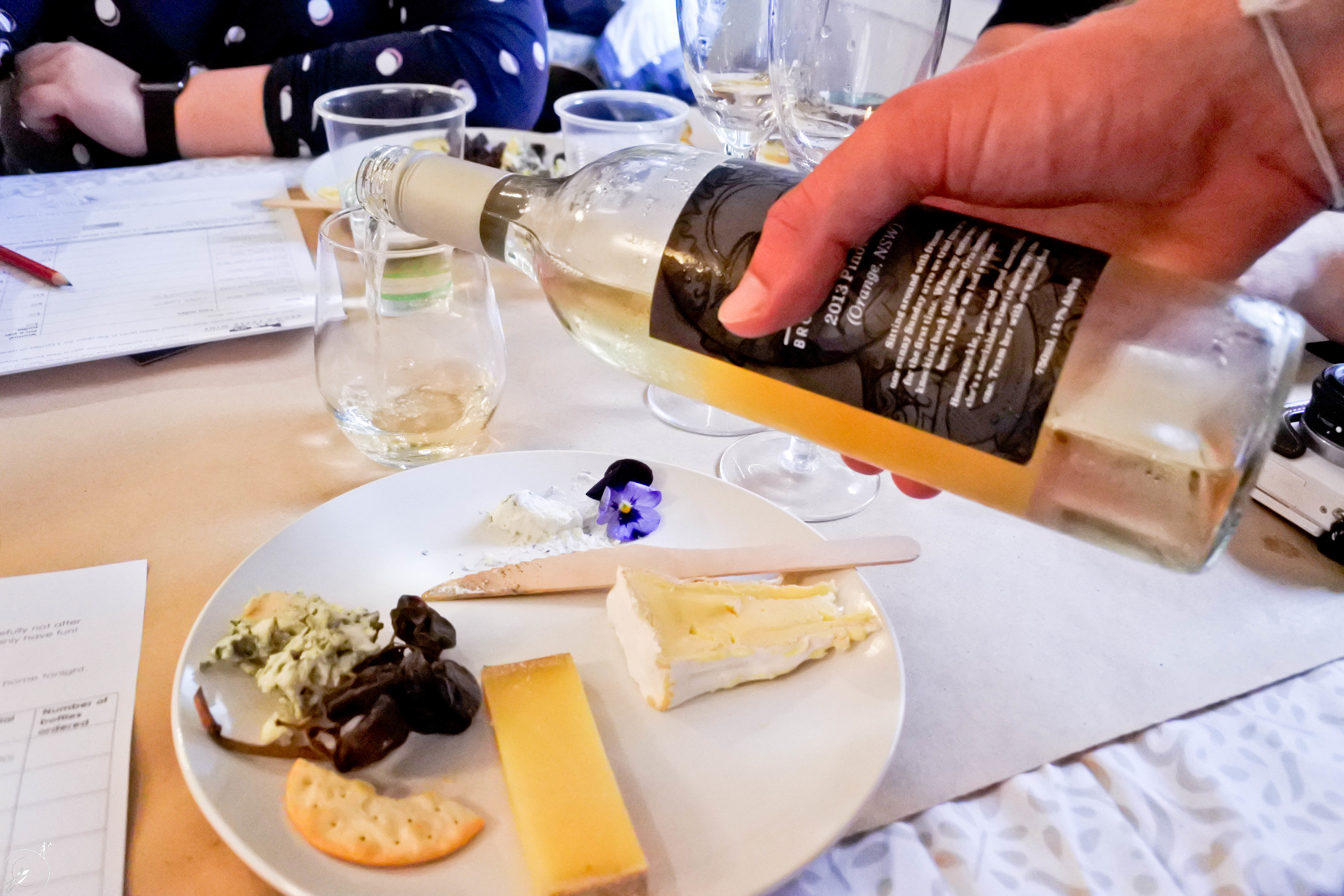 Wine poured next to cheese plate.