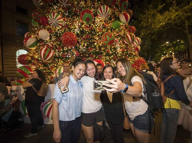 People take a selfie in front of the Christmas tree.