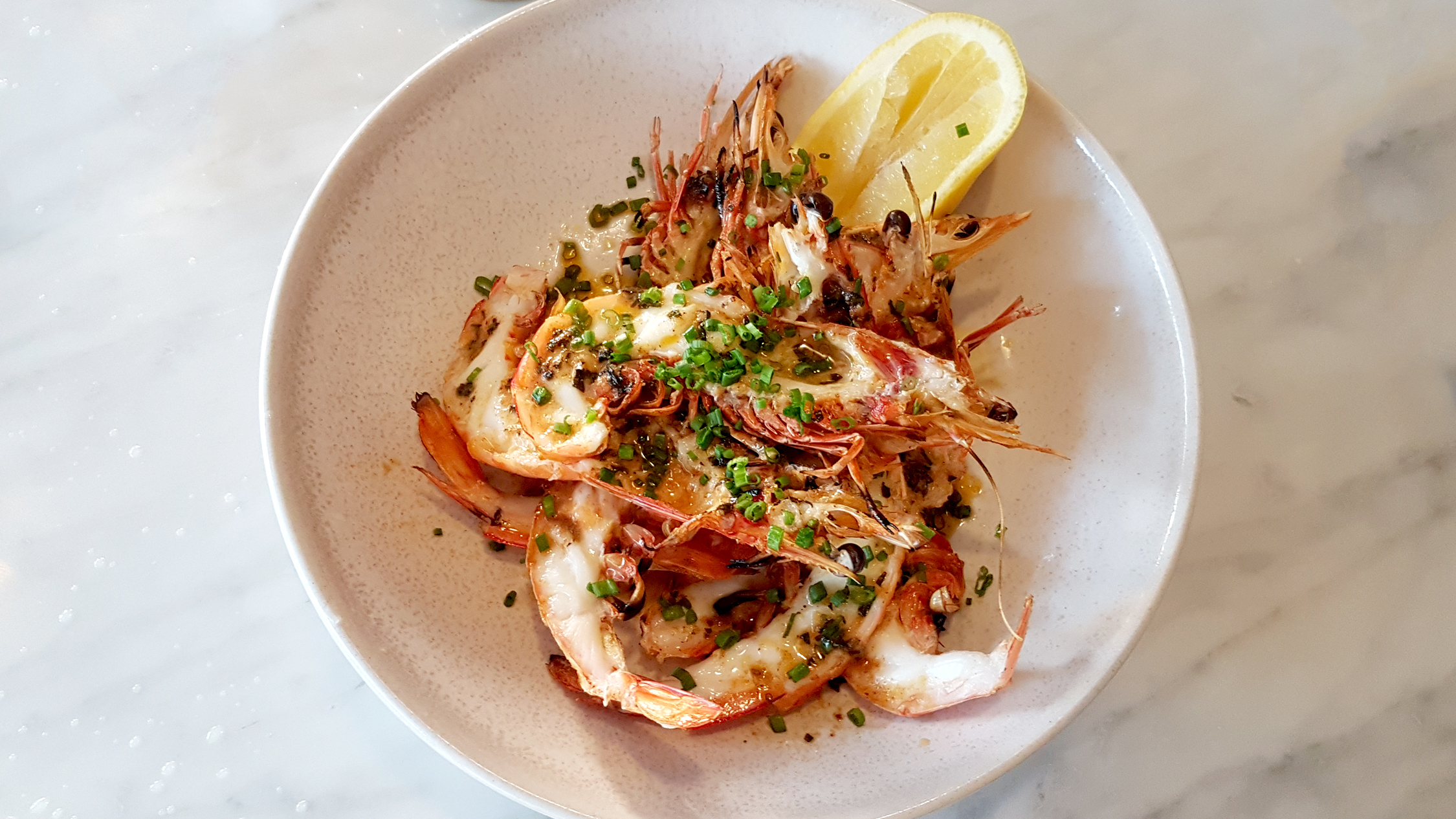 A plate of chargrilled prawns in the shell
