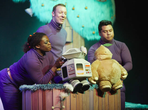 Actors and robot puppets on a stage.